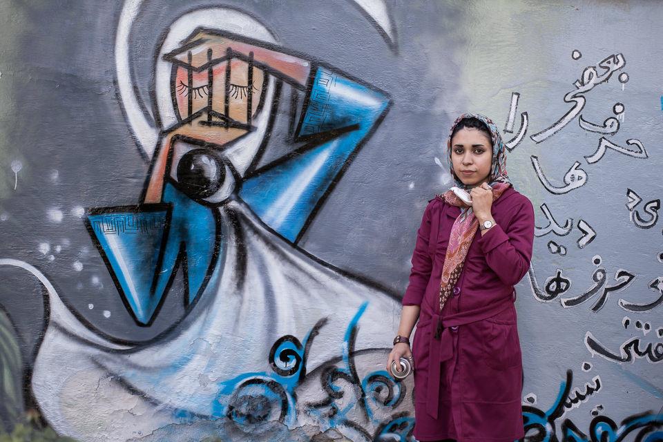 Eine Frau posiert vor einer Graffittiwand.