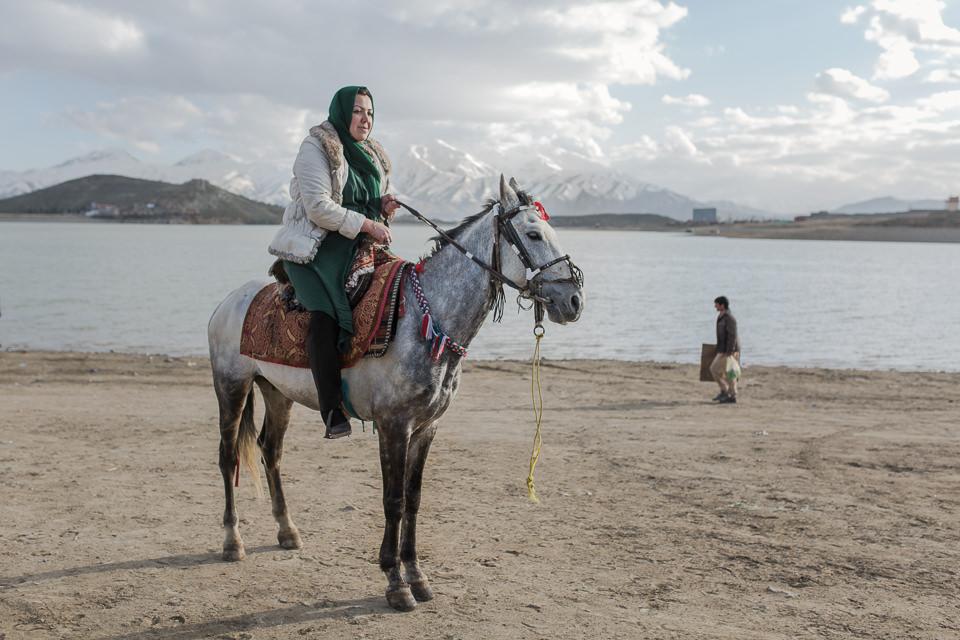 Eine Frau auf einem Pferd am Strand.