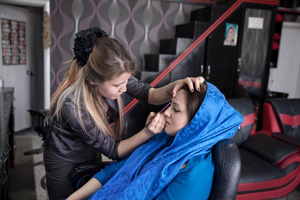 Eine Frau bekommt von einer anderen Frau die Augenbrauen gezupft.