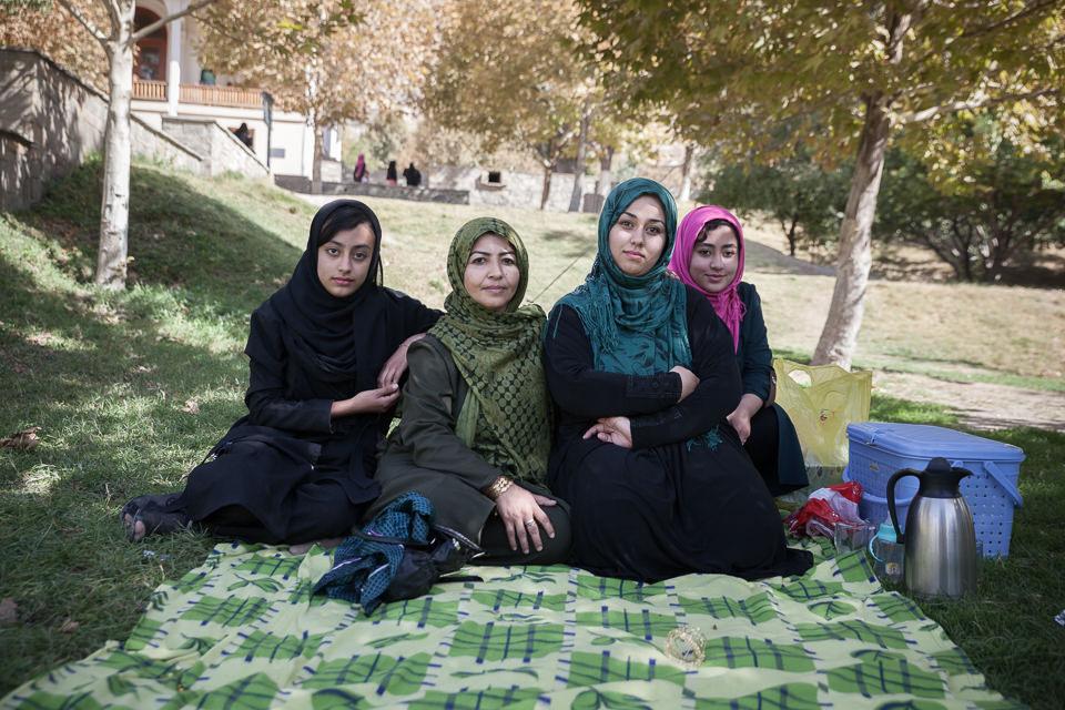 Vier Frauen sitzen auf einer Decke im Park.