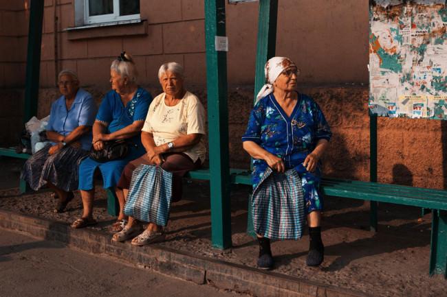 Vier Frauen mit grauen Haaren warten auf den Bus.
