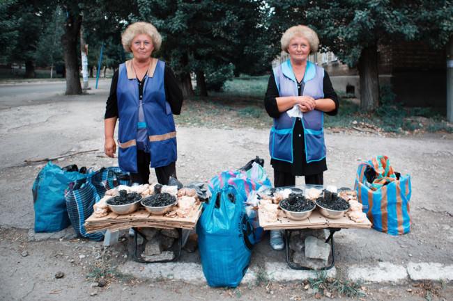 Zwillinge mit lustiger Frisur lächeln in die Kamera und verkaufen etwas.