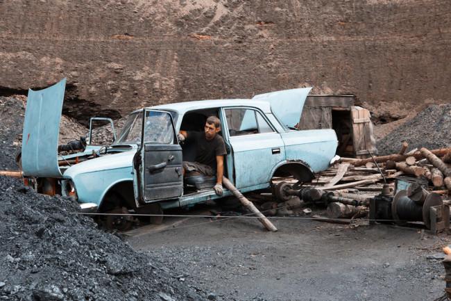 Ein Mann sitzt in einem alten Auto ohne Räder.