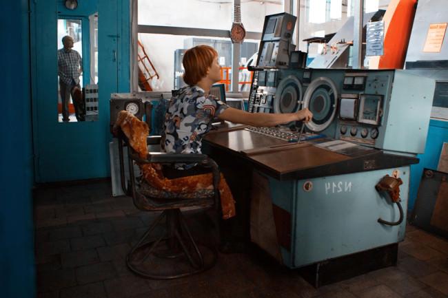 Eine Frau mit roten Haaren und Kurzhaarschnitt sitzt an alten Gerätschaften einer Industrieanlage.