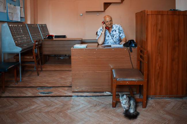 Ein Mann sitzt in einem fast leeren Raum und benutzt ein Wählscheibentelefon.