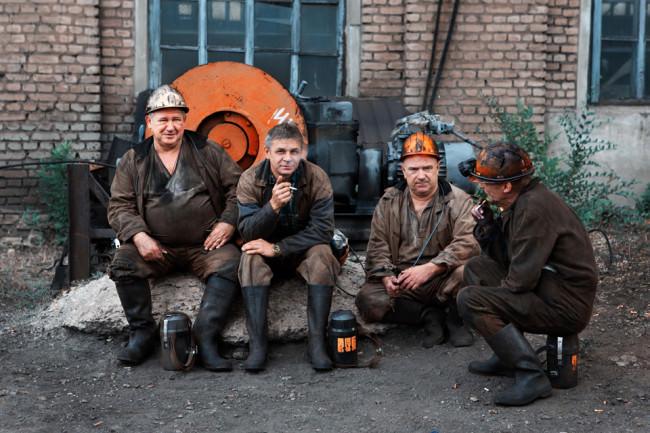 Vier Bergleute machen eine Raucherpause.