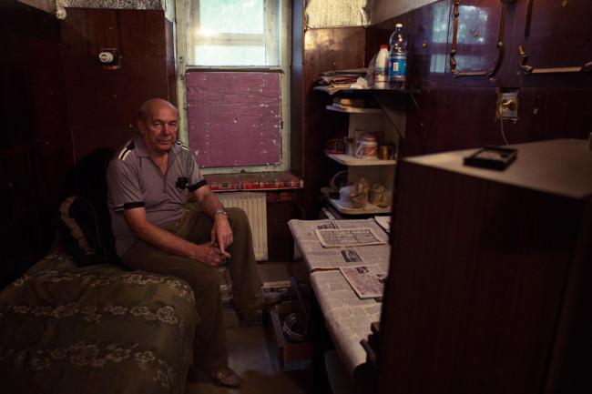 Ein Mann sitzt in seinem kleinen Zimmer und schaut fern.