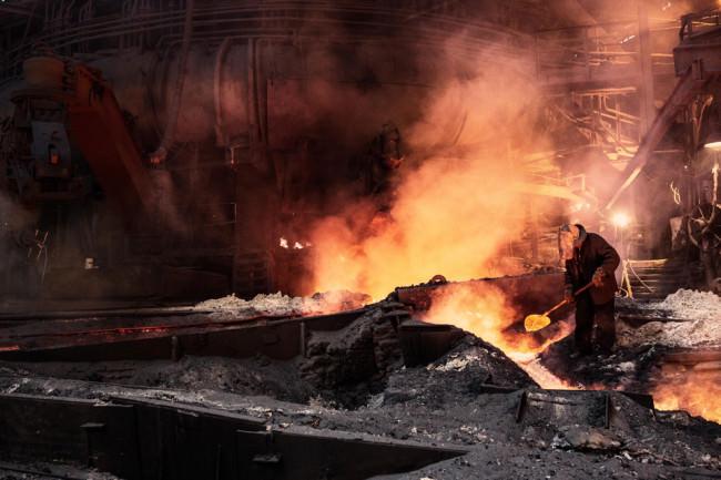 Ein Mann steht am Strom von geschmolzenem Stahl mit einer Schaufel.