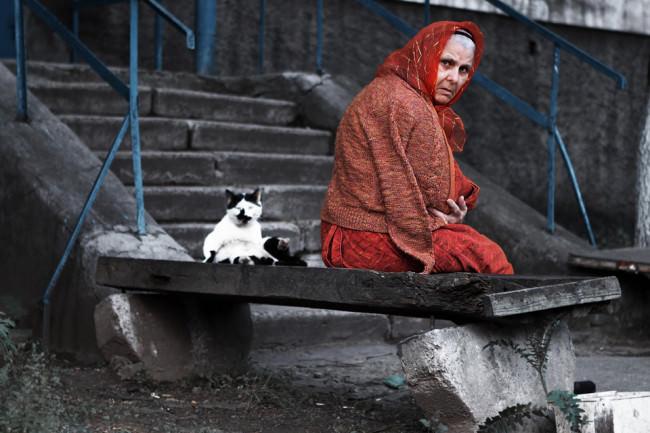 Eine alte Frau sitzt mit einer Katze auf einer Steinbank und dreht sich zum Betrachter.