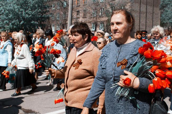 Mehrere Frauen mit roten Tulpen in der Hand gehen eine Straße entlang.