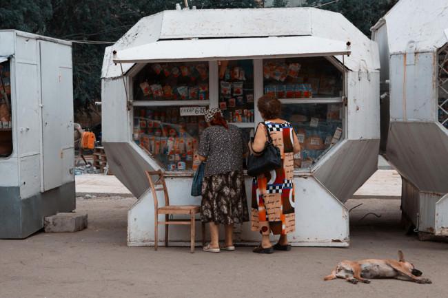 Zwei Frauen stehen vor einem Kiosk in farbenfroher Kleidung. Ein Hund schläft auf dem Asphalt.