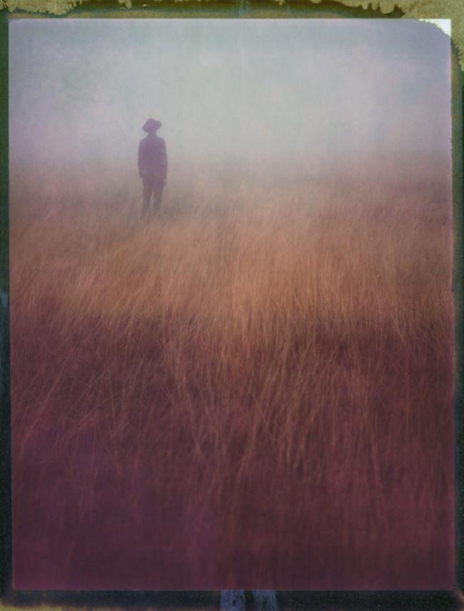 Ein Mann mit Hut steht in einem nebeligen Feld.