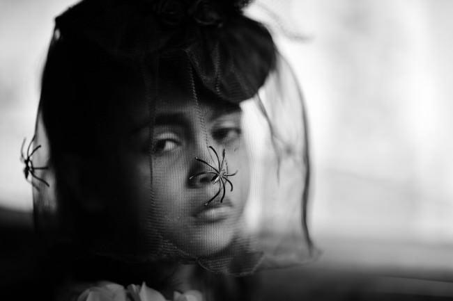 Ein Mädchen mit einem Spinnenschleier. Eine Straßenfotografie.