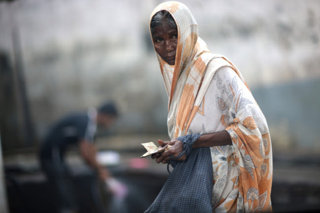 Eine Frau mit einem Notizblock und langem Tuch über dem Kopf. Eine Straßenfotografie.