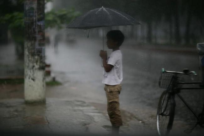 Eine Junge steht mit Schirm im Regen. Eine Straßenfotografie.