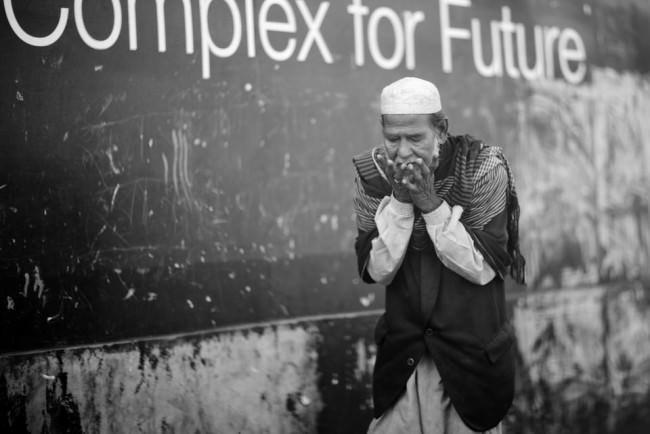 Ein Mann hält seine Hände vor sein Gesicht. Eine Straßenfotografie.