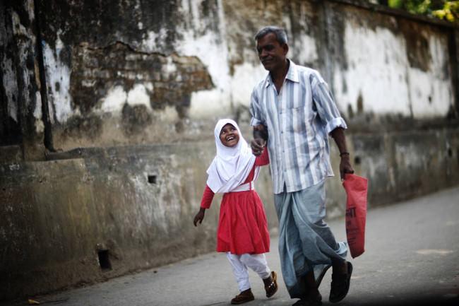 Ein Mann läuft mit seiner Tochter, die ihn anlächelt, die Straße entlang. Eine Straßenfotografie.