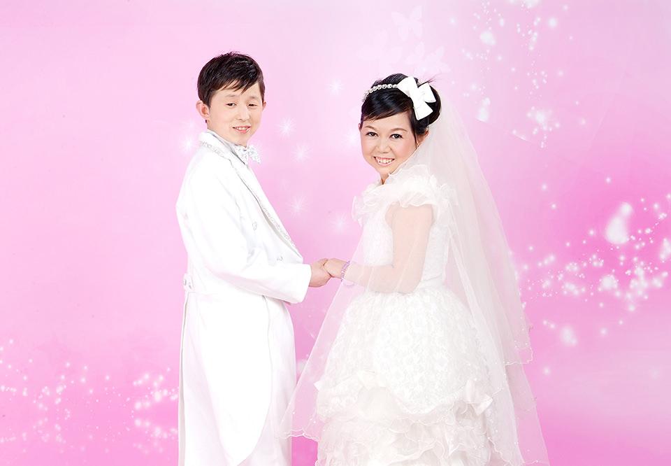 Ein Brautpaar lächelt in die Kamera und steht vor einem rosa Hintergrund mit Glitzereffekten.