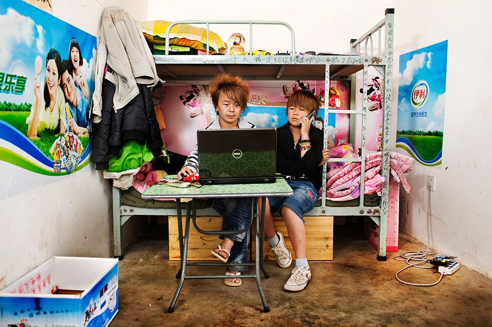 Zwei Männer sitzen auf dem unteren Bett eines Hochbettes und sehen auf einen Laptopbildschirm. Die Wände sind mit Postern tapeziert.