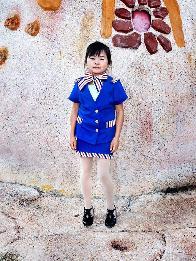 Eine Frau in blauem Anzug posiert für die Kamera vor einer Wand.