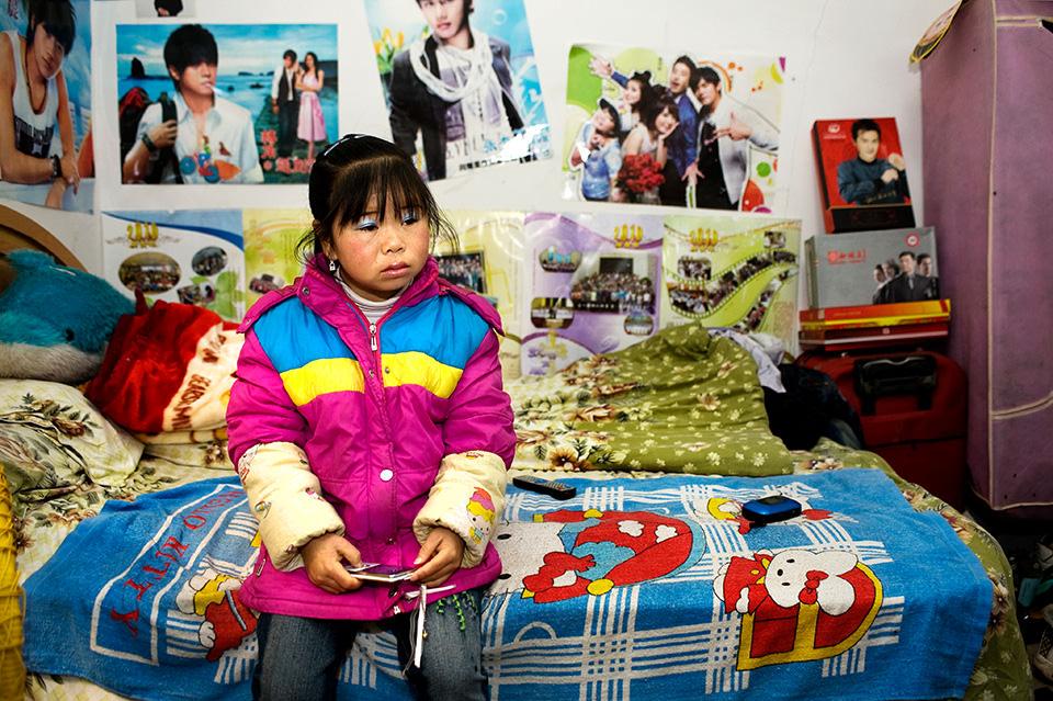 Eine Frau sitzt nachdenklich auf einem Bett. Die Wände sind mit Postern tapeziert.