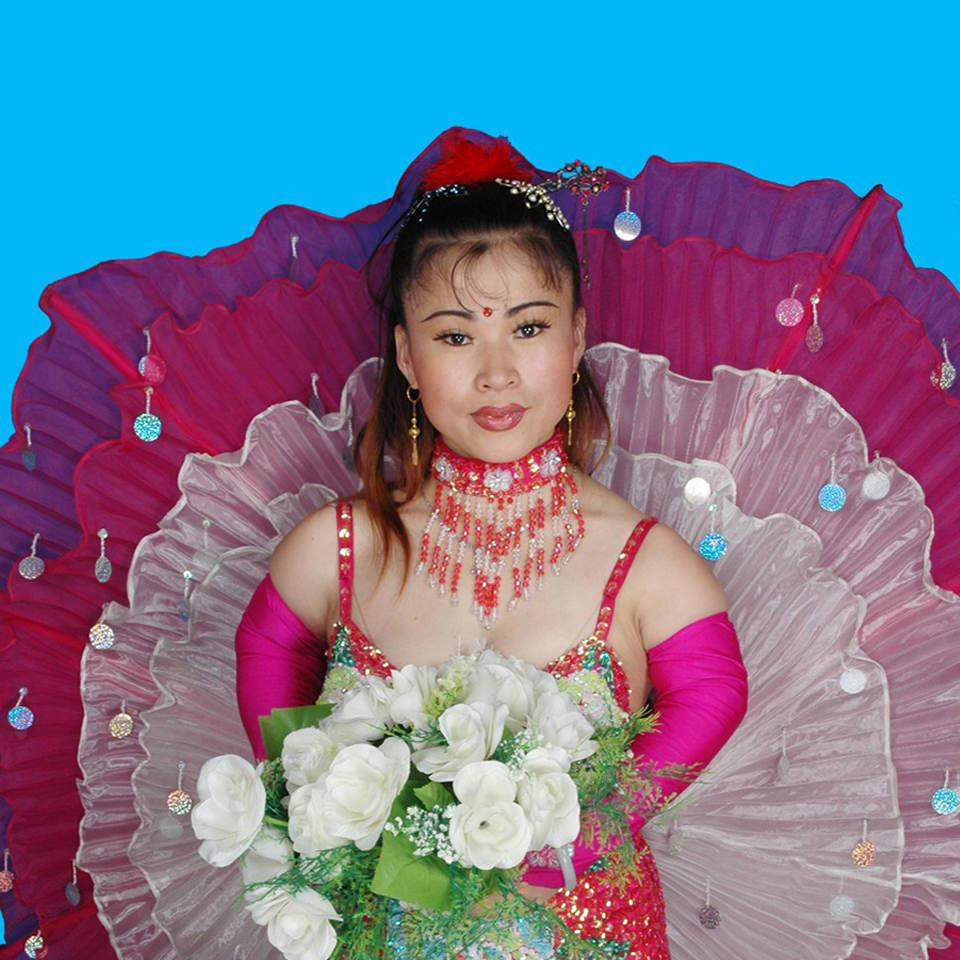 Eine Frau hält einen Blumenstrauß und trägt ein auffallendes rosa Kleid.
