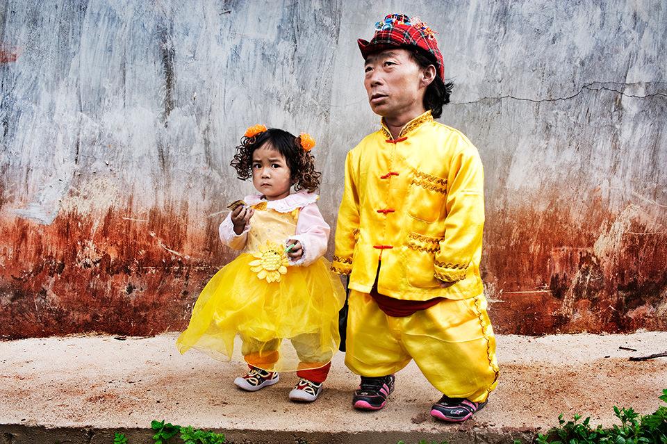 Ein Mann und ein Kind in gelber Kleidung laufen einen Weg entlang.