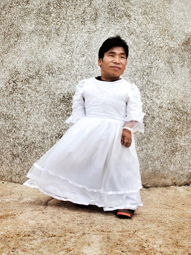 Ein Mann im Hochzeitskleid posiert vor einer Wand für die Kamera.