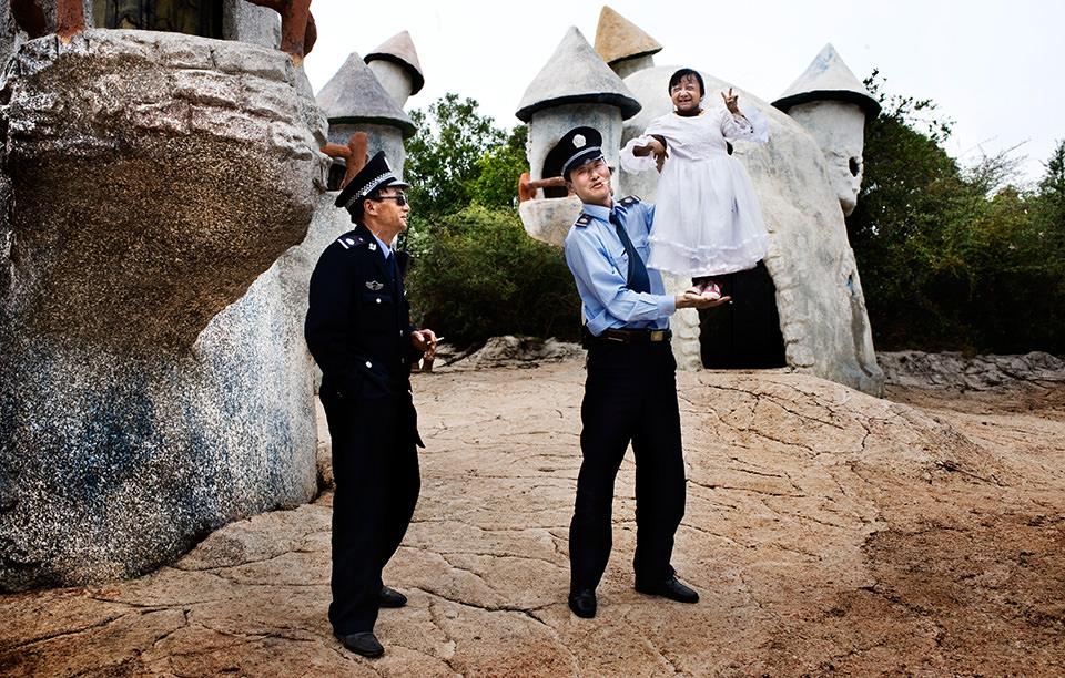 Zwei Männer in Uniform. Einer davon hält eine kleinwüchsige Frau auf seinem Arm, die in die Kamera lacht.