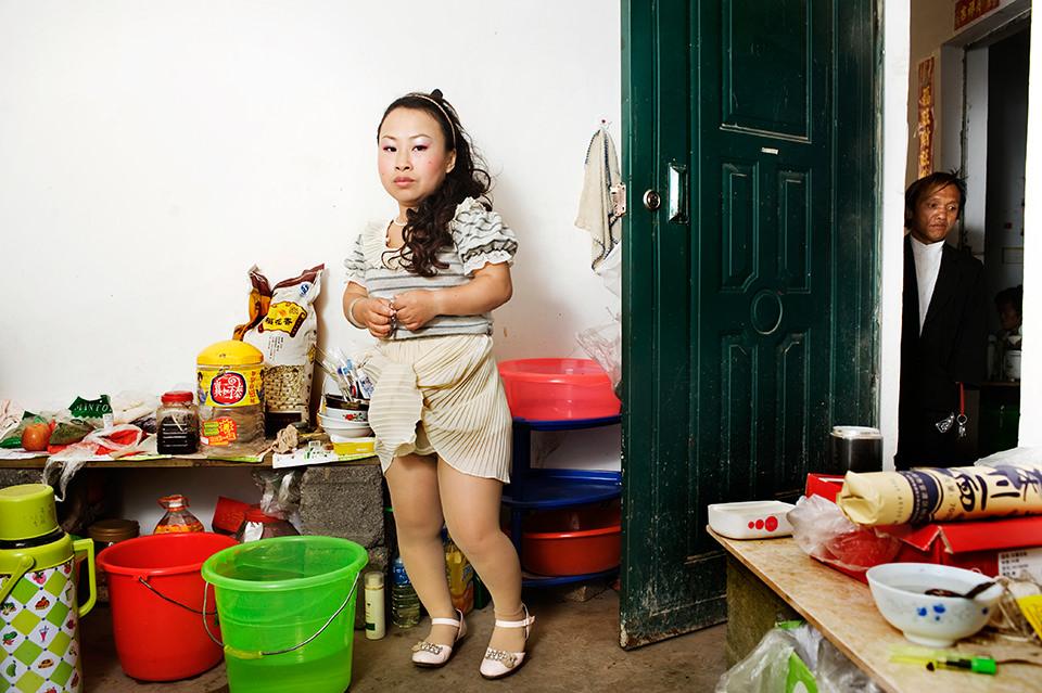 Eine Frau steht in einer unaufgeräumt wirkenden Kammer und sieht ernst in die Kamera. Rechts ist eine Tür offen, durch die man einen Mann sieht.