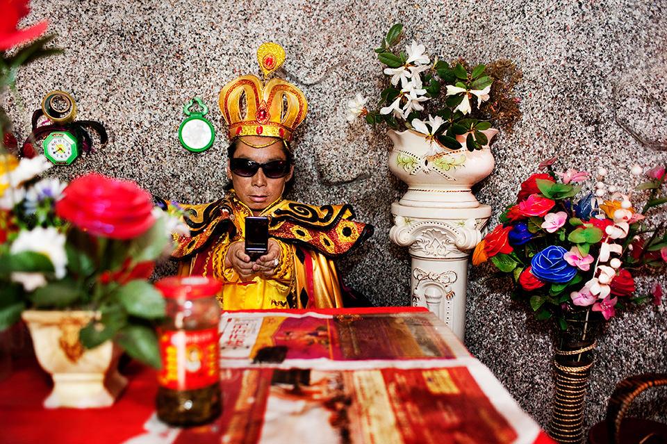 Ein Mann, als König verkleidet, trägt eine Sonnenbrille und tippt auf seinem Handy.