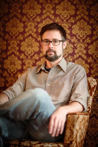 Ein Mann mit Brille sitzt vor Retrotapete in einem Retrostuhl.