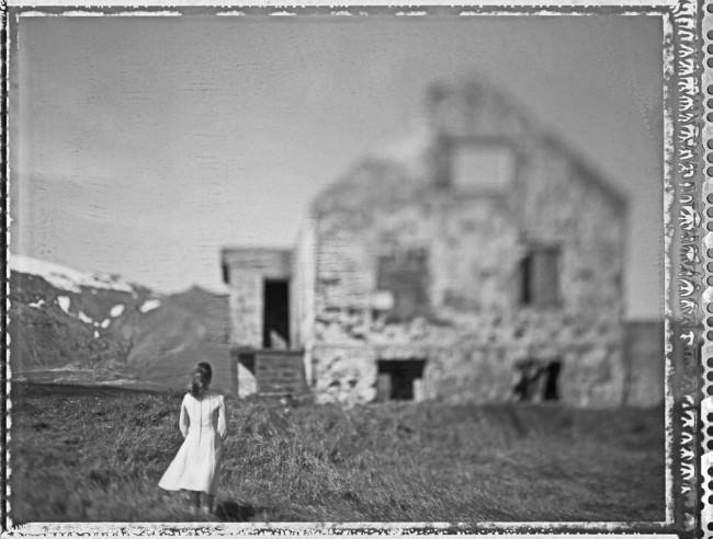 Eine Frau steht vor einem Haus, der Wind weht.