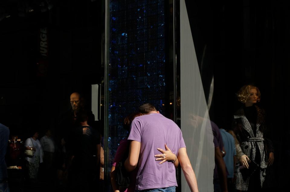 Straßenfotografie: Verdrehte Hand auf dem Rücken eines Mannes.