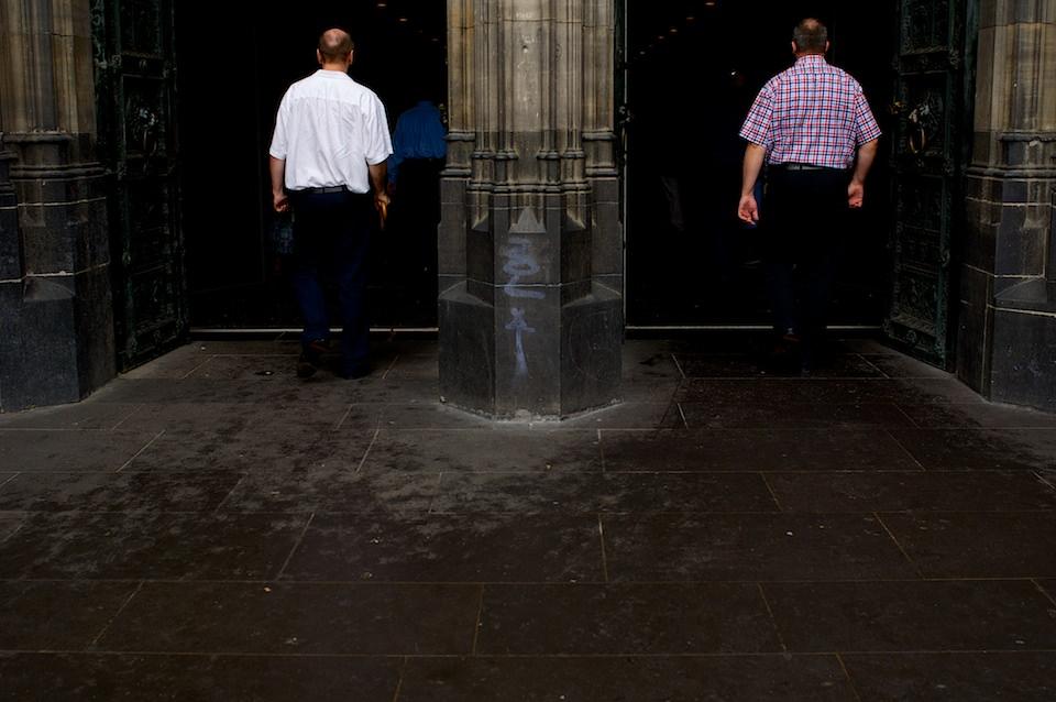Straßenfotografie: Zwei Menschen betreten eine Kirche.
