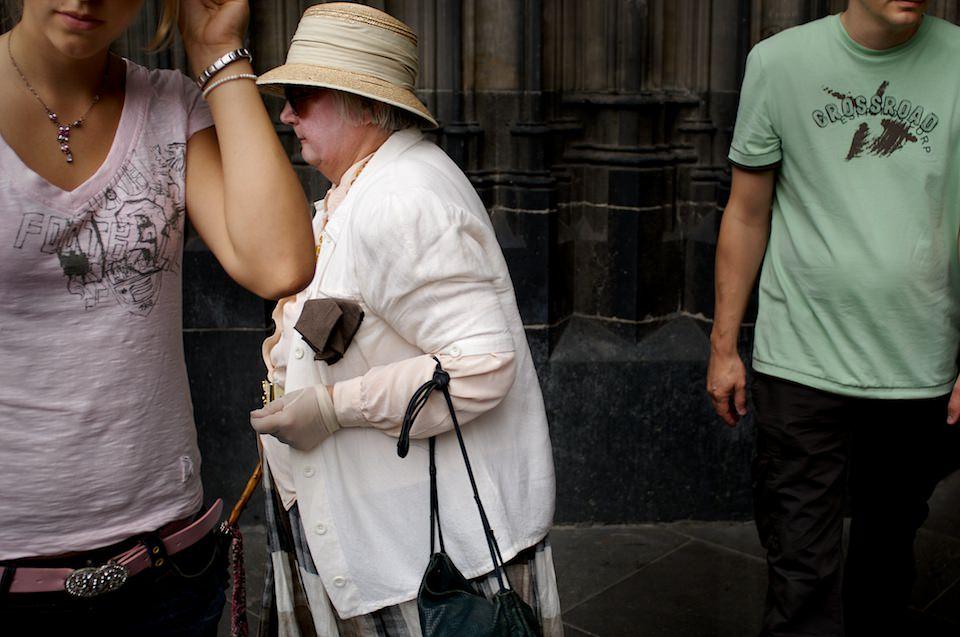 Straßenfotografie: Fokus auf eine ältere Frau mit Hut.