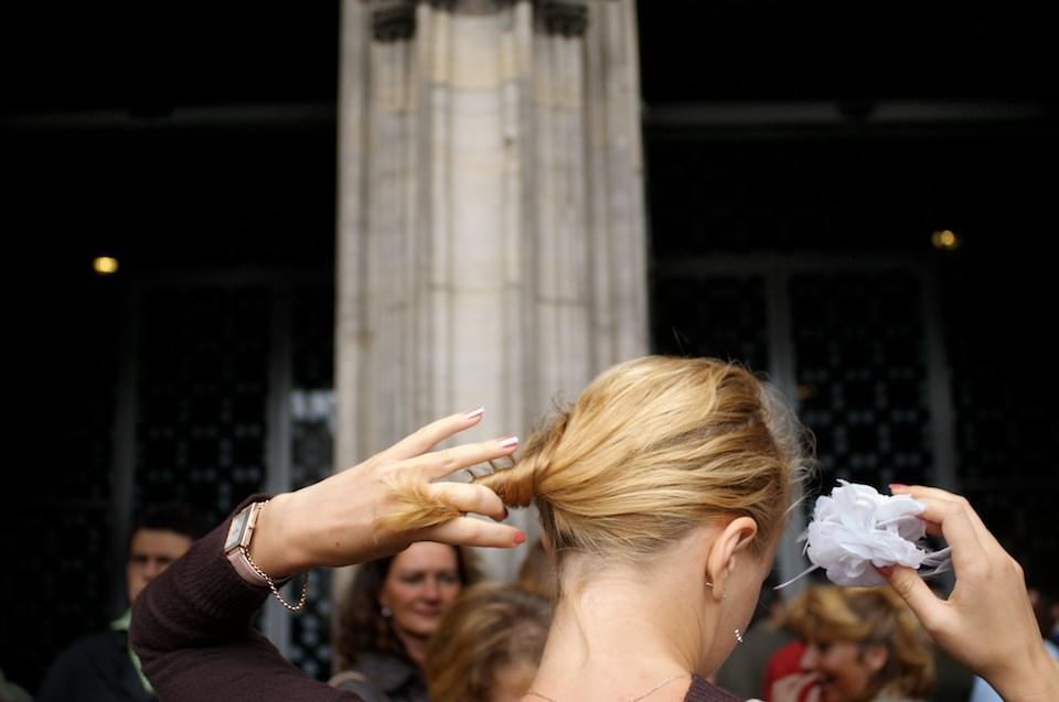 Straßenfotografie: Eine Frau zwirbelt an ihrem Haar.