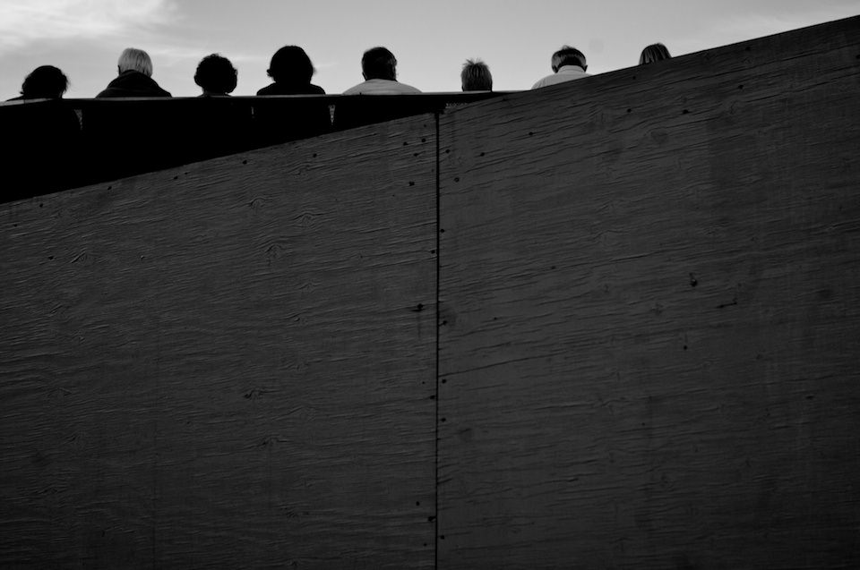 Straßenfotografie: Eine Wand von hinten, oben schauen Köpfe von Menschen hervor.