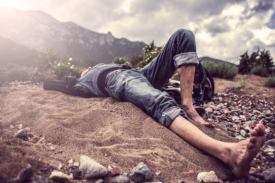 Portrait: Ein Mann ruht sich auf dem Boden aus.