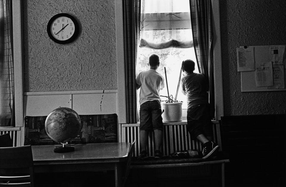 Zwei Jungs schauen gemeinsam zum Fenster hinaus.
