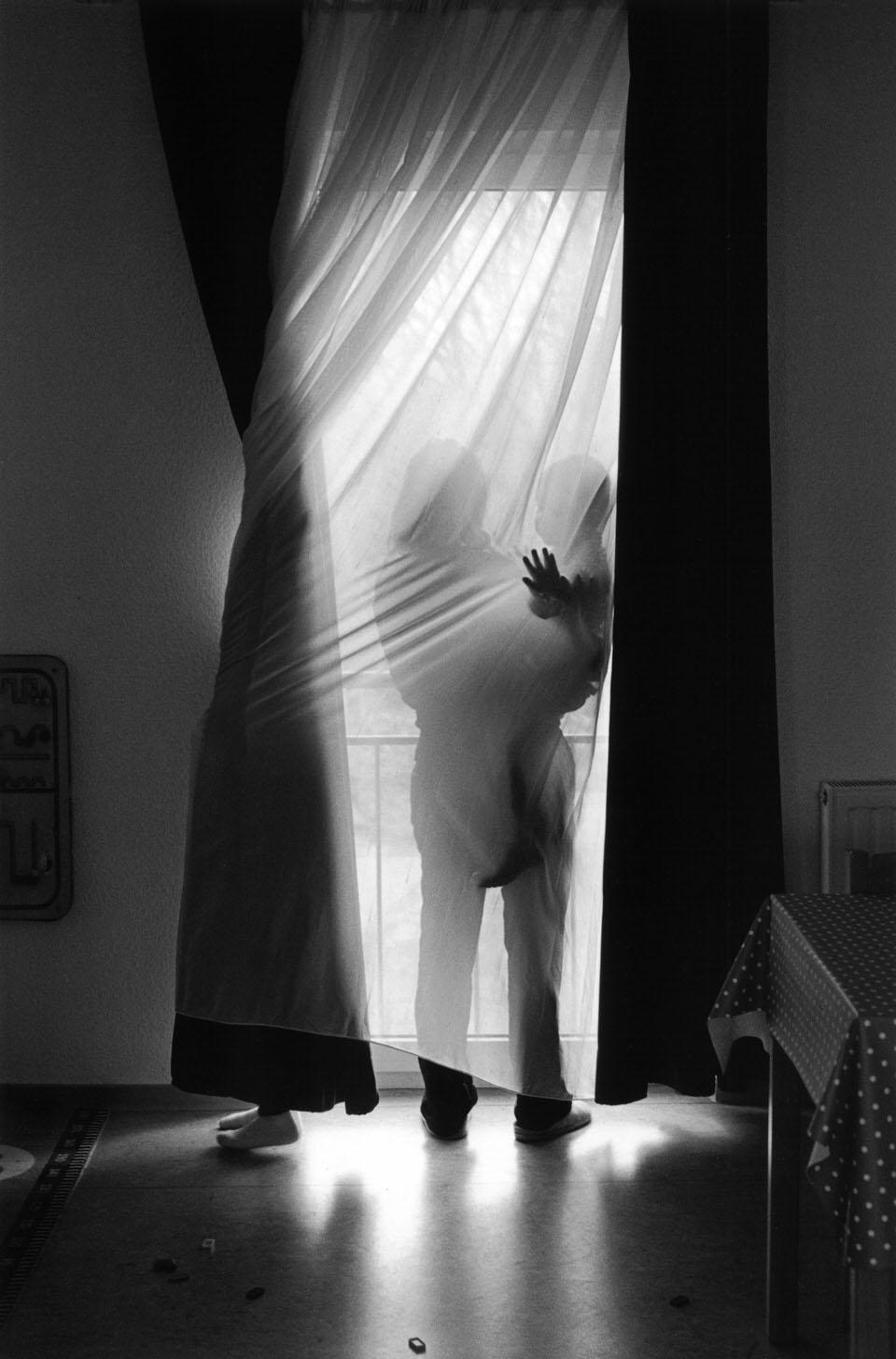 Eine Frau steht mit ihrem Kind am Fenster, neben ihr dreht sich ein zweites im Vorhang.