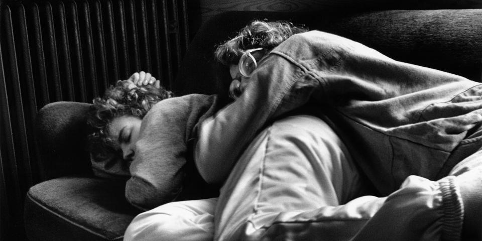 Titelbild: Eng umschlungen liegen zwei Frauen auf der Couch.