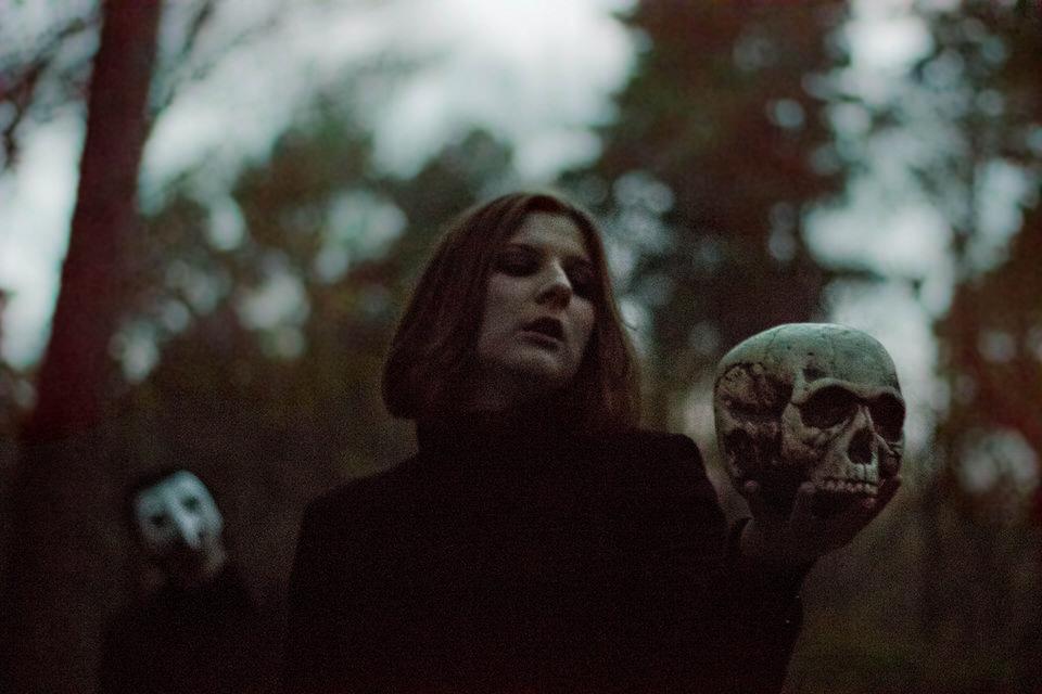 Eine Frau im Wald mit einem Totenkopf in der Hand.