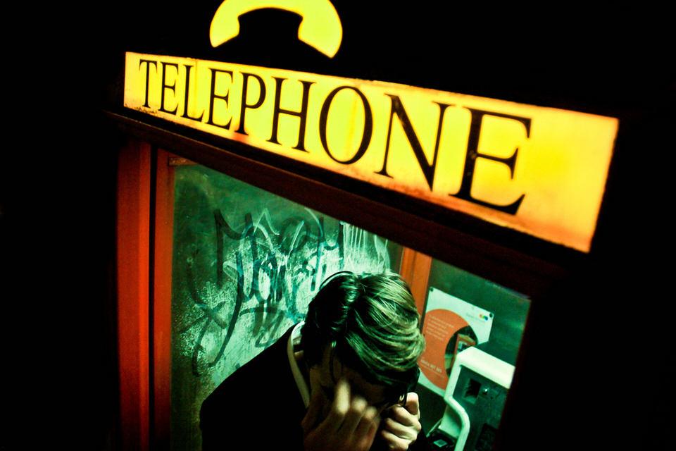 Portraitaufnahme von einem Mann in der Telefonzelle.