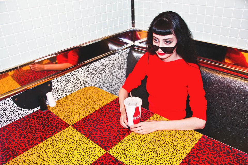 Eine Frau mit rotem Pulli sitzt an einem gelb-roten Tisch.