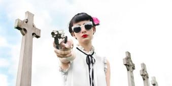 Ein Portrait einer Frau mit Pistole in der Hand.