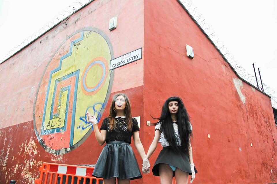 Zwei Frauen vor einem Gebäude.