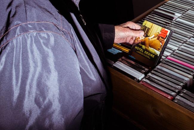 Ein Mann zieht eine Erotik-DVD heraus.