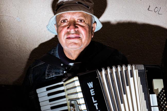 Ein Mann spielt auf der Ziehharmonika –an der Wand hinter ihm steht LOL.