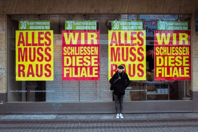 Eine Frau steht von einer Fensterscheibe mit Plakatierungen zum Ausverkauf.